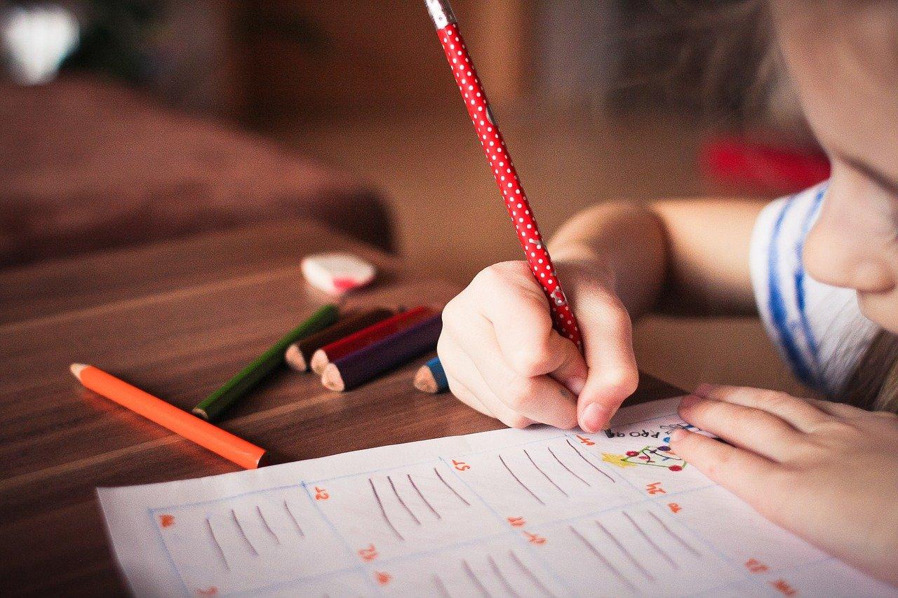 机に向かって文字を書く子ども