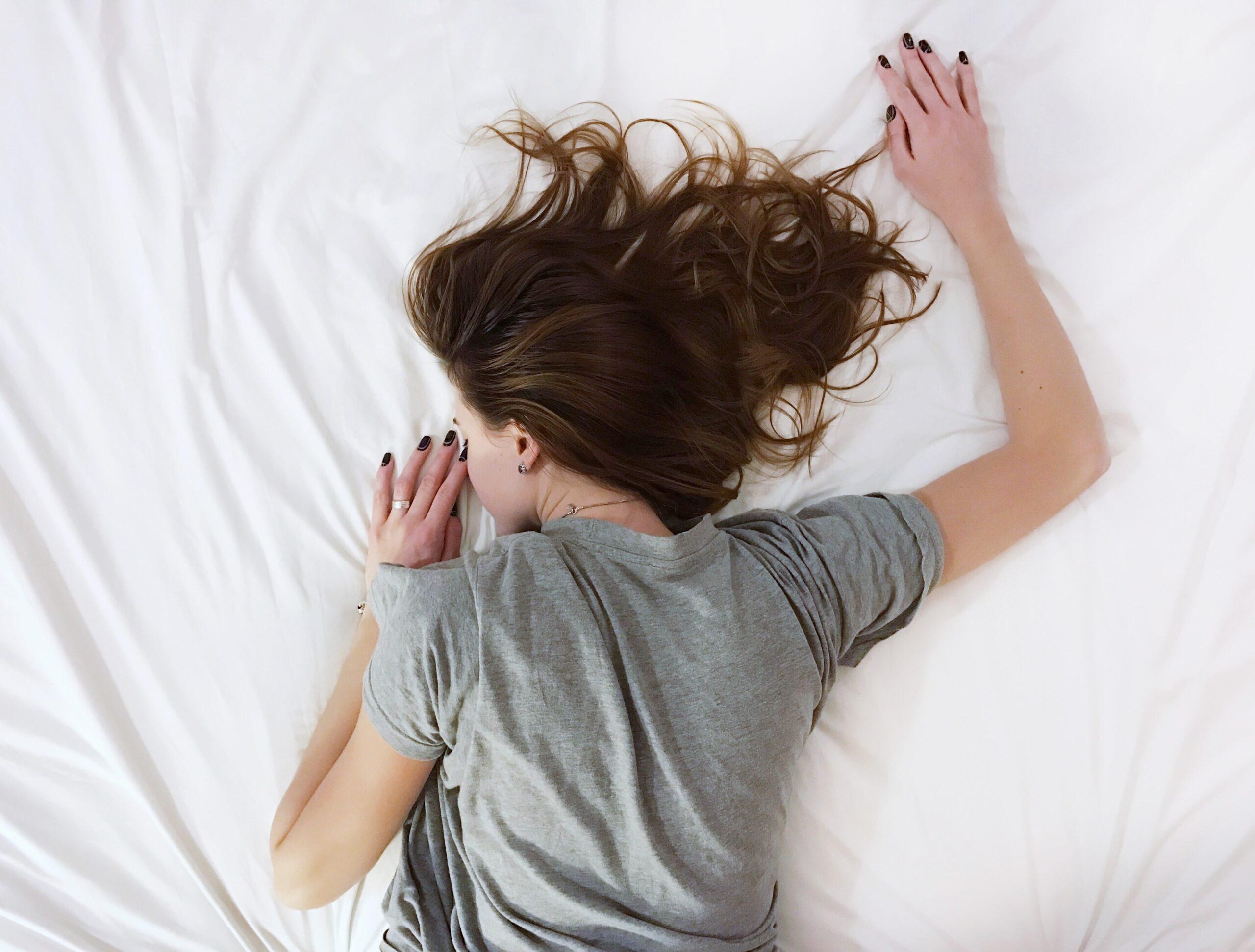布団に伏せる疲れてしまった女性女性