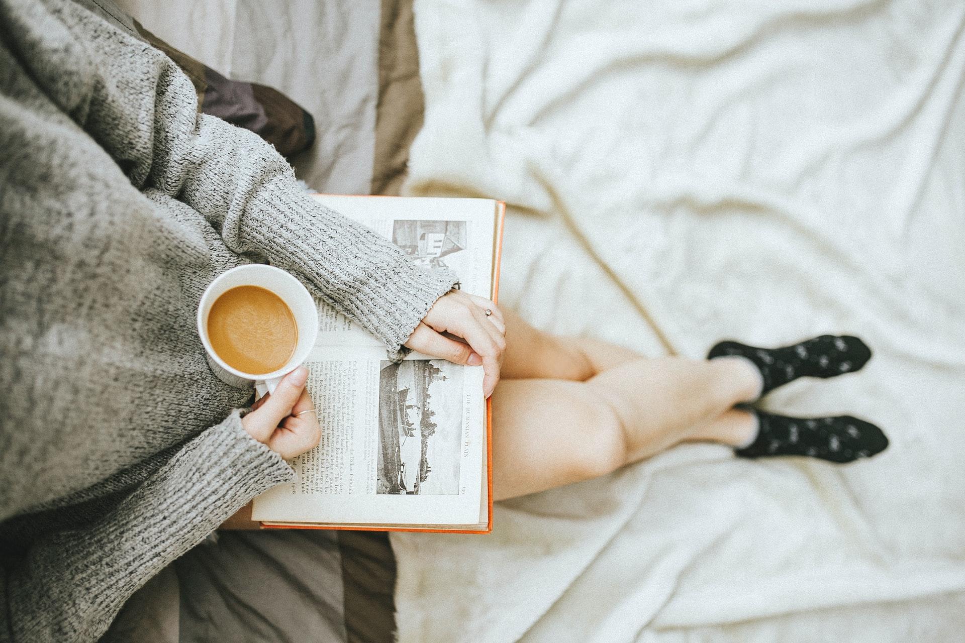 コーヒーを片手にし膝に本を置いて座る女性