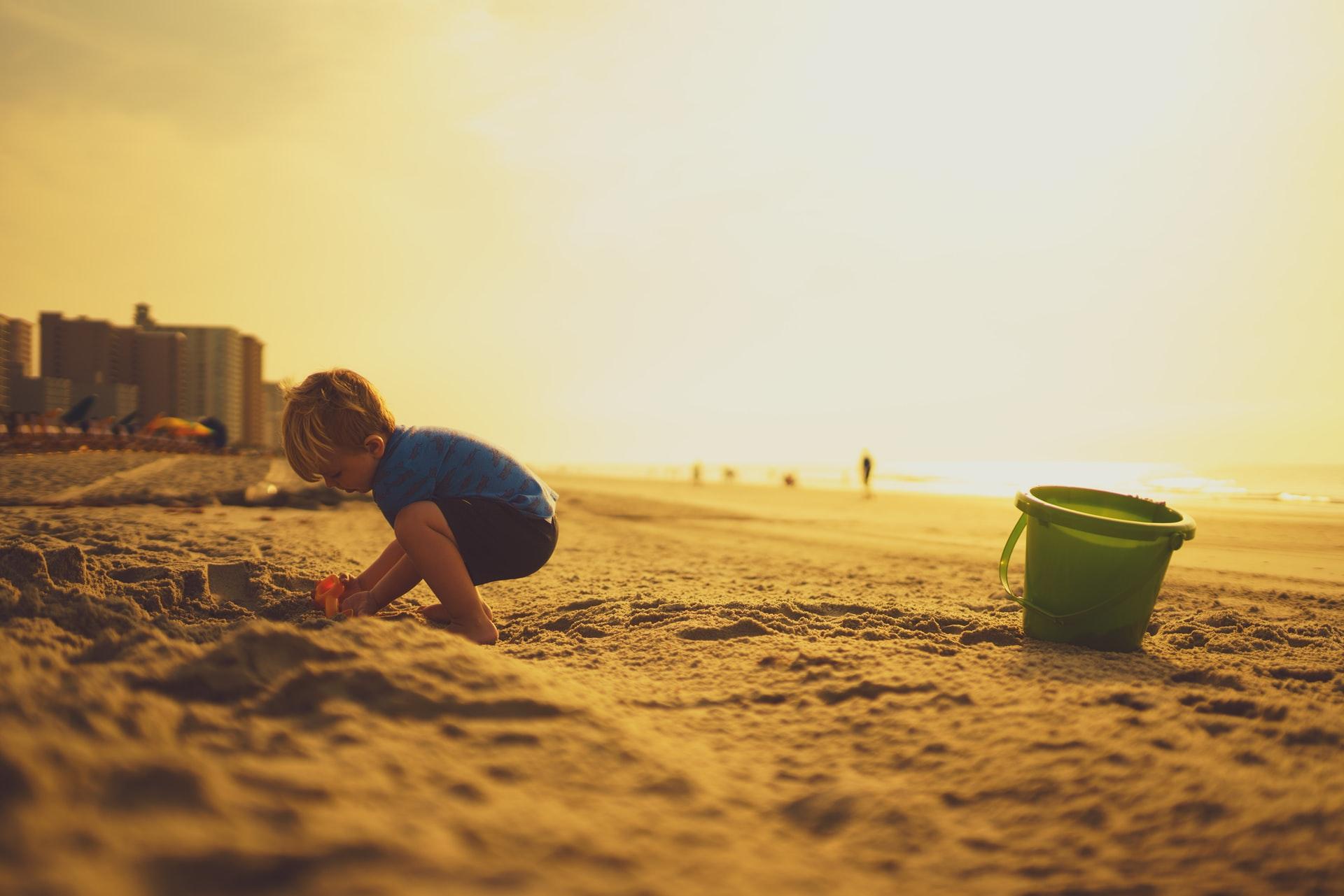 バケツを置いて砂浜で遊ぶこども