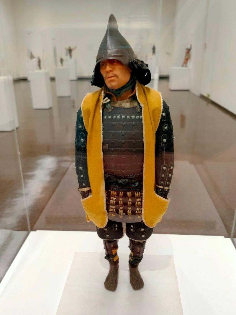 鎧を纏い黄色いベストのポケットに手を入れる人のフィギュア