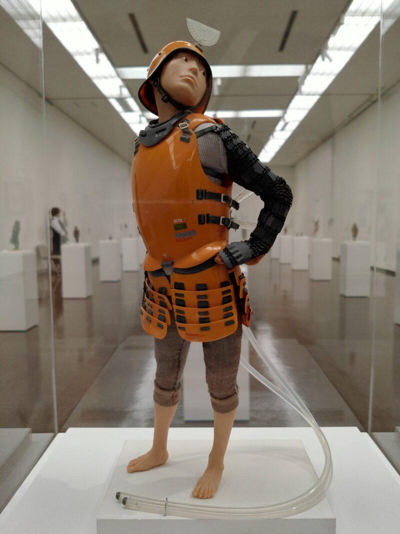 プラスチックの鎧を纏い背中につながれたチューブをのぞき込む人のフィギュア