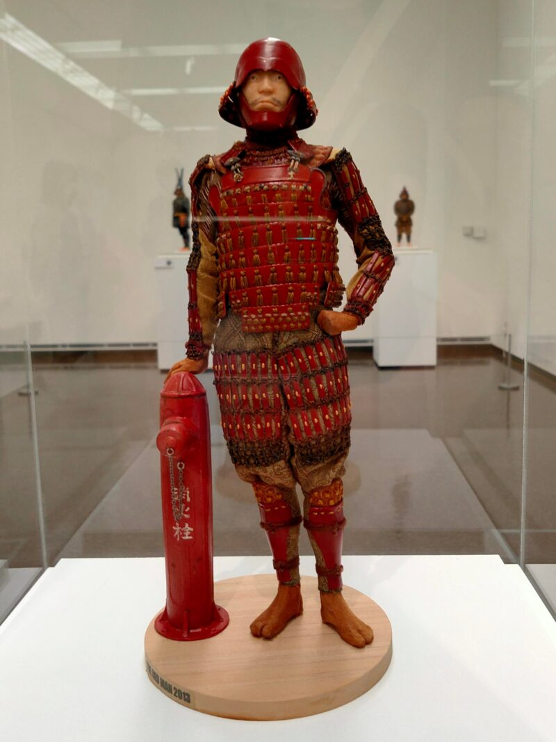 赤い鎧を纏い消火栓にもたれかかる人のフィギュア